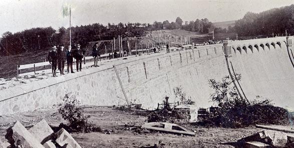 Das Foto wurde am 30.9.1908 aufgenommen, sieben Wochen vor Inbetriebnahme der Neye-Talsperre, aufgenommen. Bei den Personen handelt es sich vermutlich um Vertreter der Stadt und der Baufirma. Foto: EWR GmbH.