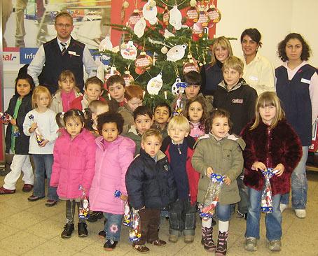 Oberbürgermeisterin Wilding gemeinsam mit den Kindern der Kita Struck, der Erzieherin Nadine Leonhardt (li.) und der Mutter Britta Sieckendieck (re.) vor dem soeben geschmückten Tannenbaum.